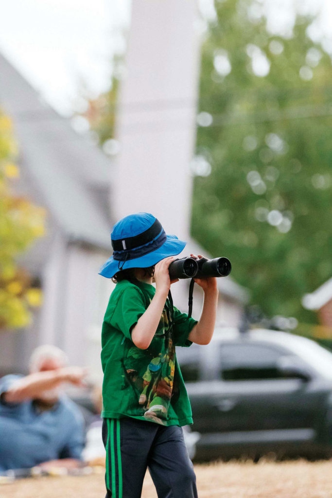 A young boy with binoculars getting ready for the migrating event.
