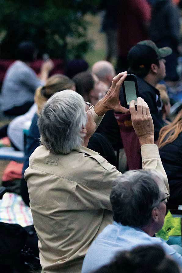 An elder gentleman looking at his phone as he tries to capture an image of the birds migrating.