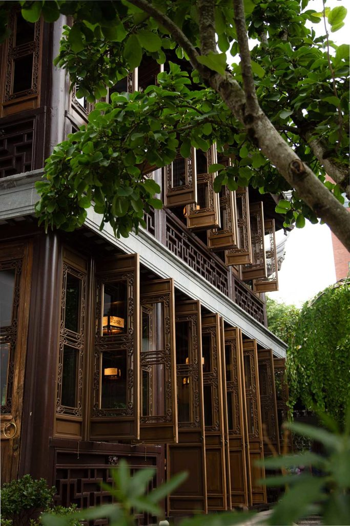 The outside of a Chinese teahouse with long slender windows peering out at a large tree