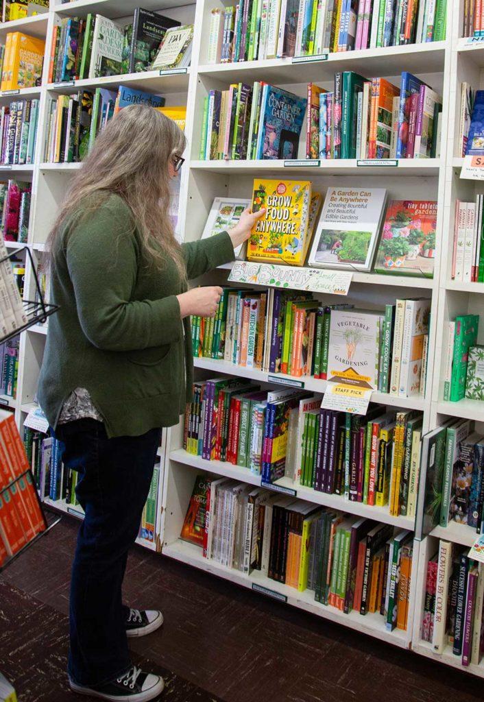 A woman grabbing a book off of a shelf in a book store