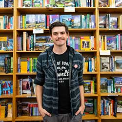 A man smiling in front of a bookshelf in a book store